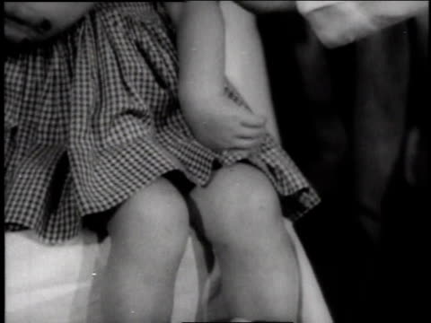 little girl wearing boots getting salk vaccine / kansas, usa - 1957 stock-videos und b-roll-filmmaterial