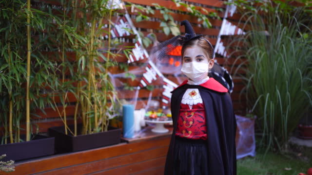 little girl wearing face mask on halloween party during covid-19 pandemic - count dracula stock videos & royalty-free footage