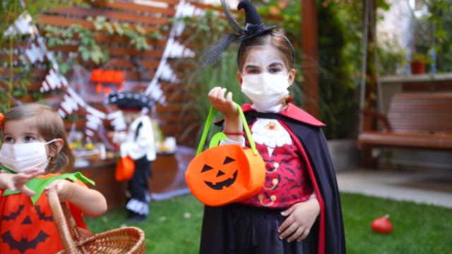stockvideo's en b-roll-footage met meisje dat gezichtsmasker op partij van halloween tijdens covid-19 pandemie draagt - graaf dracula