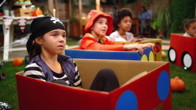 vidéos et rushes de petite fille utilisant le costume de pirate avec ses amis à la nuit de film d'halloween - se déguiser