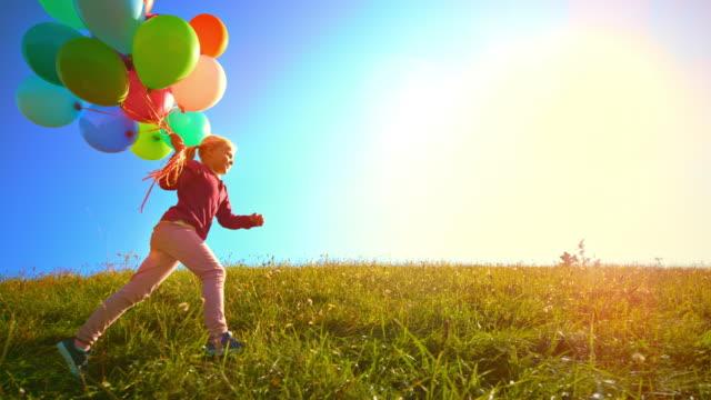 カラフルな風船の束で日当たりの良い草原で走るポニーテールを身に着けているslo moリトルガール - side view点の映像素材/bロール