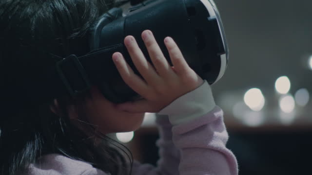 little girl wearing virtual reality glasses - innovazione video stock e b–roll