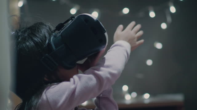 vídeos de stock e filmes b-roll de little girl wearing virtual reality glasses - competência