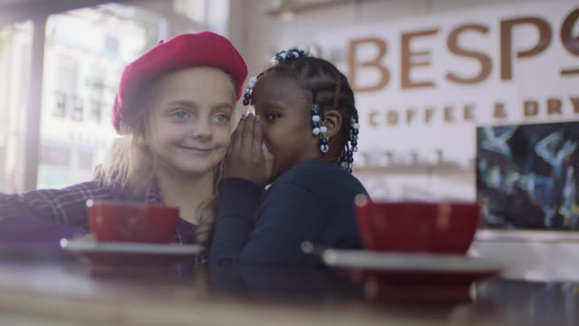 ms. little girl whispers a secret and giggles with her friend in cute coffee shop. - flüstern stock-videos und b-roll-filmmaterial
