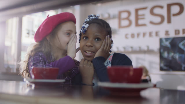 MS. Little girl whispers a secret and laughs with her friend in cute coffee shop.