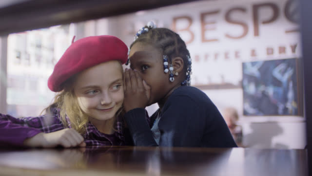 MS. Little girl whispers a secret to her friend in cute coffee shop.