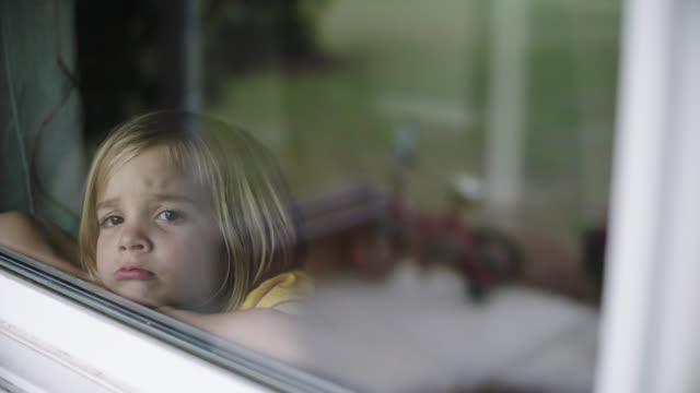 slo mo. little girl wishing she could go outside. - quarantena video stock e b–roll