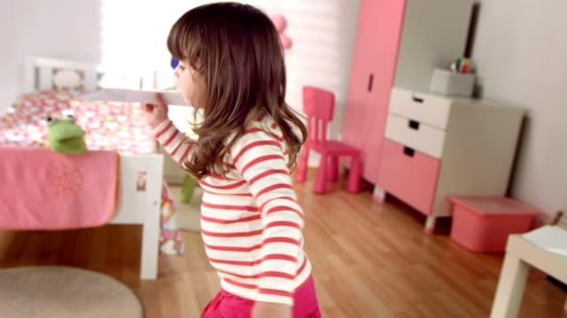 vídeos y material grabado en eventos de stock de hd cámara lenta: niña con un avión de papel - avión de papel