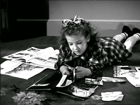 B/W 1949 little girl with bow in her hair lying on floor cutting out pictures from magazine