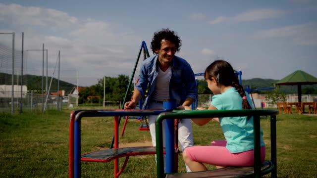お父さんと小さな女の子はカルーセルに回転します - gフォース点の映像素材/bロール