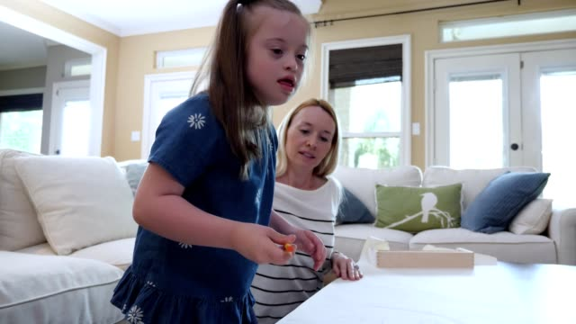 little girl with down syndrome enjoys coloring with her mom - mental disability stock videos & royalty-free footage