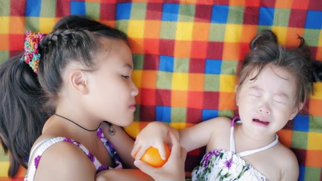 kleines mädchen mit ihrer kleinen schwester, aber sie fängt an zu weinen - streiten stock-videos und b-roll-filmmaterial