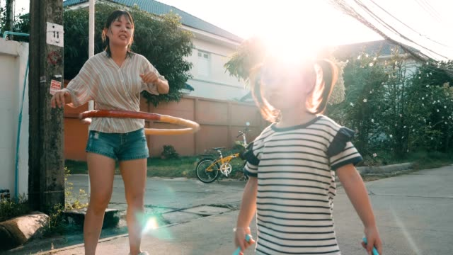 little girl with her mother jumping rope and playing hula-hoop - skipping along stock videos & royalty-free footage