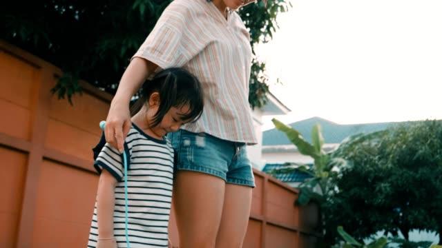 vídeos de stock e filmes b-roll de little girl with her mother jumping rope at dusk - corda de saltar