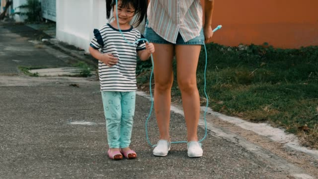little girl with her mother jumping rope at dusk - skipping along stock videos & royalty-free footage