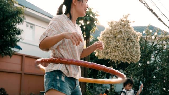 vídeos de stock e filmes b-roll de little girl with her mother playing hula-hoop together - corda de saltar