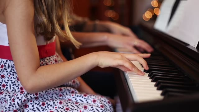 little girl with her mother playing the piano at christmas - 40 sekunden oder länger stock-videos und b-roll-filmmaterial