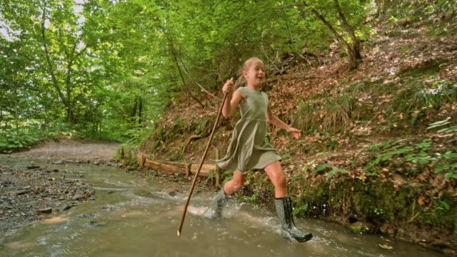 森の中の小さなクリークで中棒を保持している長い髪の slo mo の少女 - 棒切れ点の映像素材/bロール