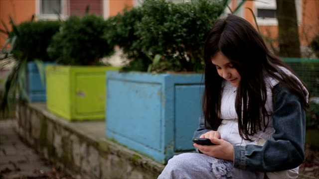 Little girl with mobile phone typing sms
