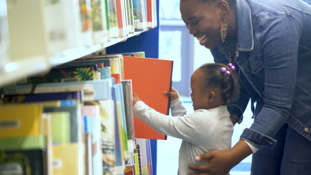 little girl with mother at the library - bookshelf stock videos & royalty-free footage