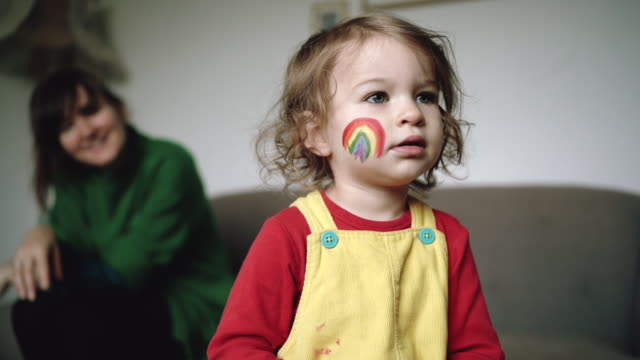 little girl with painted rainbow on cheek - annual event stock videos & royalty-free footage