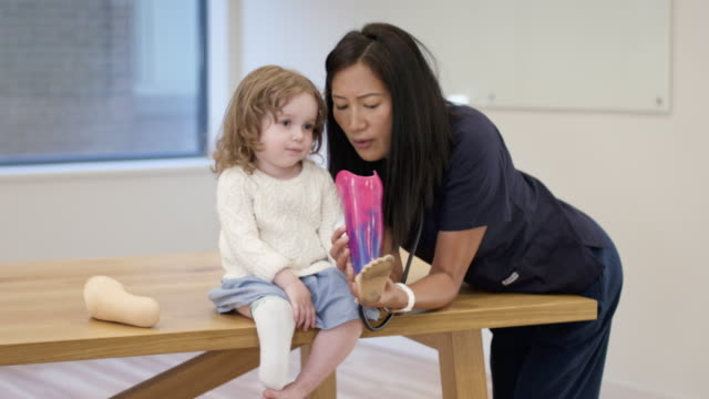 little girl with prosthetic leg at medical appointment - prosthetic equipment stock videos & royalty-free footage