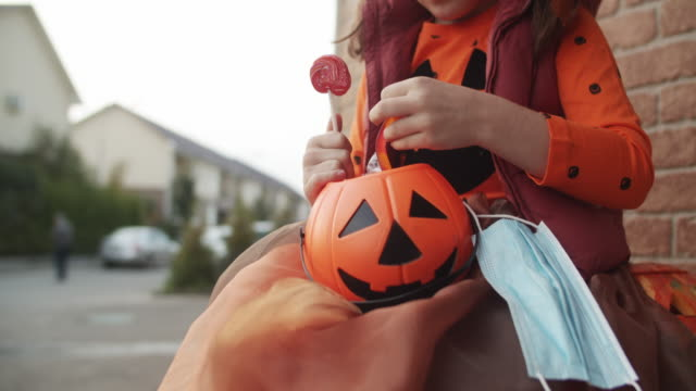 ハロウィーンのキャンディーとお菓子で彼女のバスケットを見て保護フェイスマスクを持つ小さな女の子 - 菓子類点の映像素材/bロール