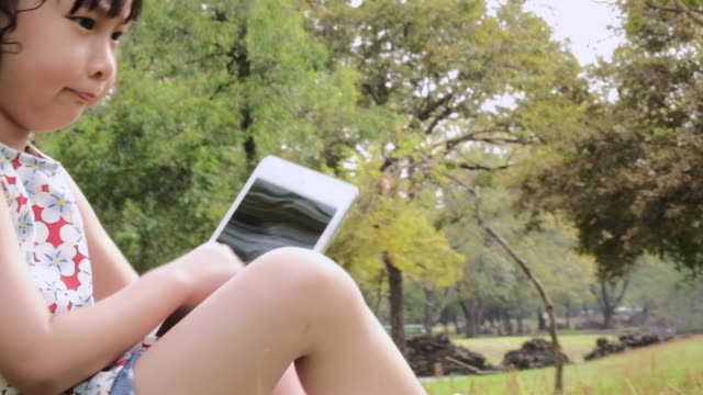 vidéos et rushes de petite fille avec les tablet pc et casque d'écoute de la musique ou regarder la vidéo dans le parc de l'été. - pavé tactile