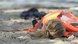 Little girl with trauma taking off life vest, lying on beach after shipwreck