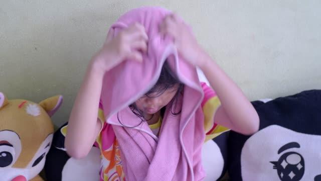 濡れた髪の小さな女の子がタオルで覆われています。