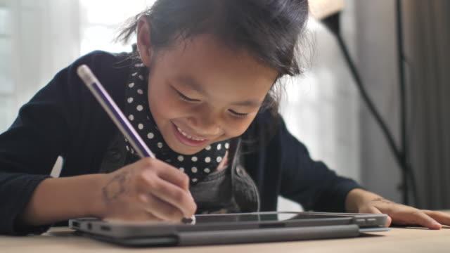 vidéos et rushes de petite fille écrivant la tablette numérique pour le penchant et l'éducation - synthpop
