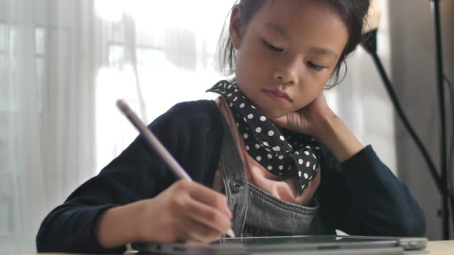 little girl writing homework on digital tablet for leaning and education at home - leaning stock videos & royalty-free footage