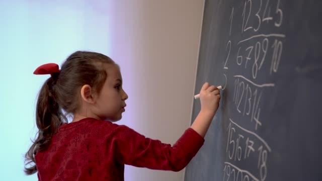 Little girl writing numbers on blackboard