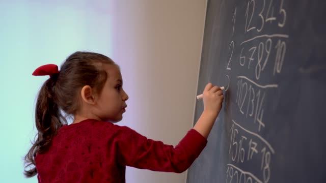 kleines mädchen schreibt zahlen auf tafel - auflösen stock-videos und b-roll-filmmaterial