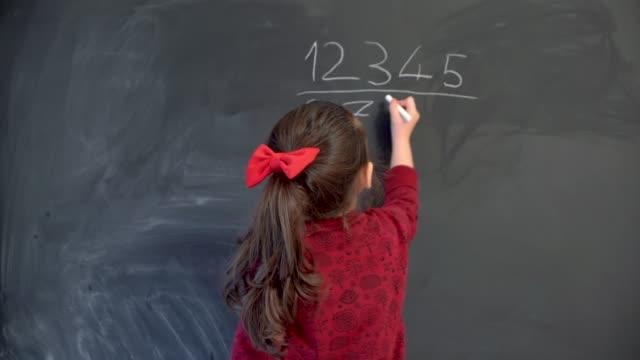 little girl writing numbers on blackboard - ozgurdonmaz stock videos and b-roll footage