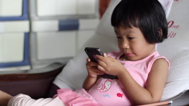 vídeos y material grabado en eventos de stock de niñas asiáticas usando el teléfono inteligente en casa - nativo digital