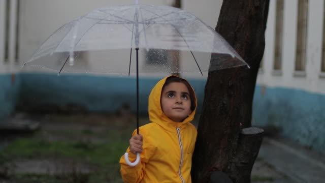 little girls having a happy time in the rain - umbrella stock videos & royalty-free footage