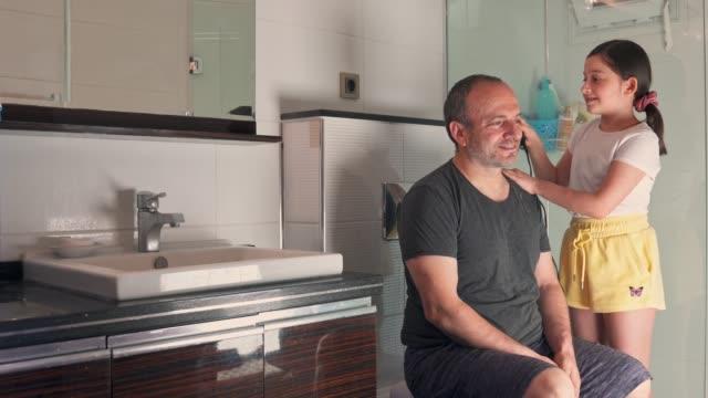 vídeos de stock, filmes e b-roll de garotinhas se divertindo cortando o cabelo do pai - estilo de cabelo