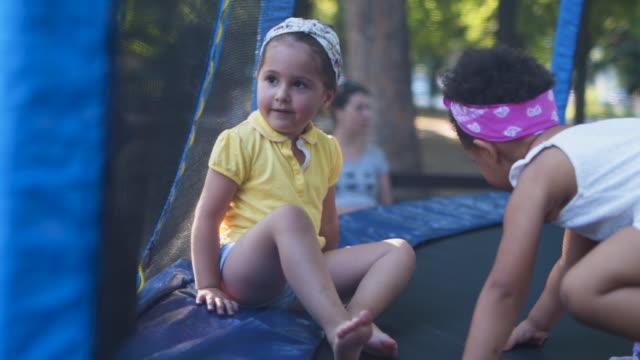 vídeos de stock e filmes b-roll de little girls jumping together on a trampoline - trampolim equipamento desportivo