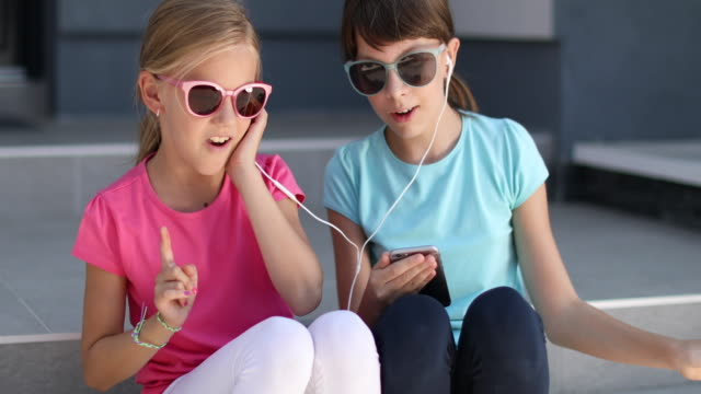 little girls listening music on smart phone and singing - cuffia attrezzatura per l'informazione video stock e b–roll