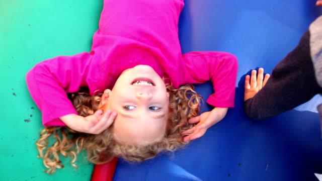 背中の上に横たわる女の子弾む城で遊ぶ - 2歳から3歳点の映像素材/bロール