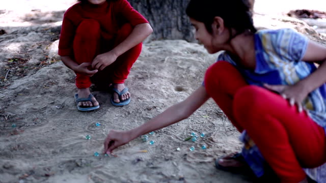 Little girls playing Marbles