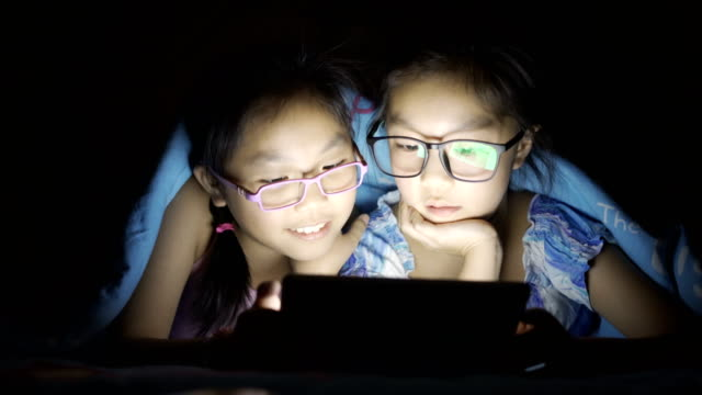 little girls plays digital table at night - sibling stock videos & royalty-free footage