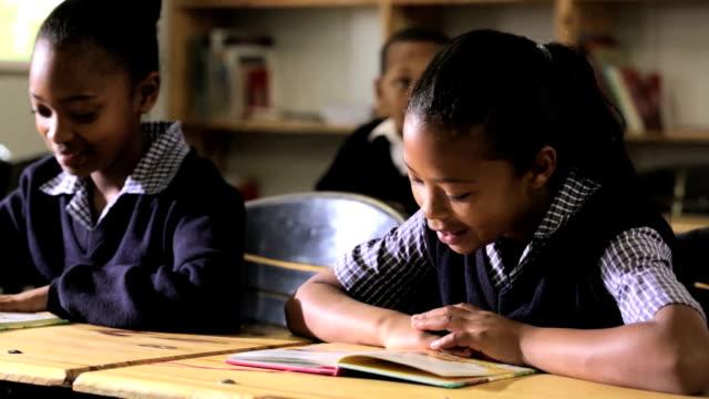 Little Girls read in class as teacher checks them