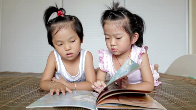 Little girls reading a picture book on bed /Xi'an, Shaanxi, China