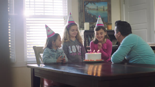 WS. Little girls sing Happy Birthday as dad brings birthday cake in to family dining room.
