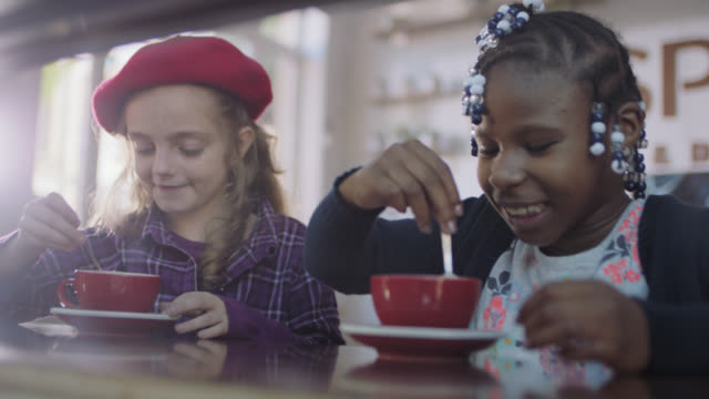 vídeos de stock, filmes e b-roll de ms. little girls stir hot chocolate in mugs and sip from spoons in coffee shop. - boina