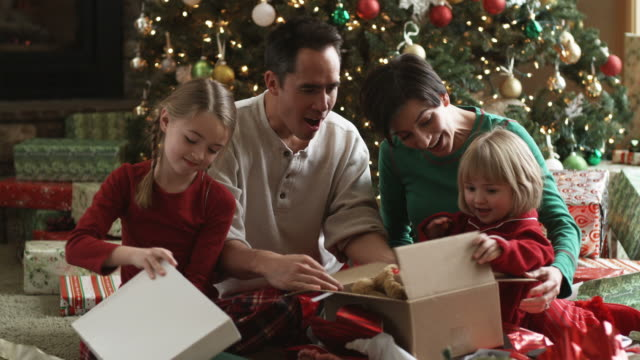 vidéos et rushes de little girls trading gifts on christmas morning - noël