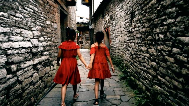 vídeos y material grabado en eventos de stock de niñas que caminan en un viejo callejón, anshun, guizhou, china. - encuadre de cuerpo entero