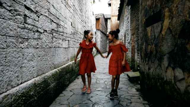 vídeos de stock e filmes b-roll de little girls walking in a old alley,anshun,guizhou,china. - full length